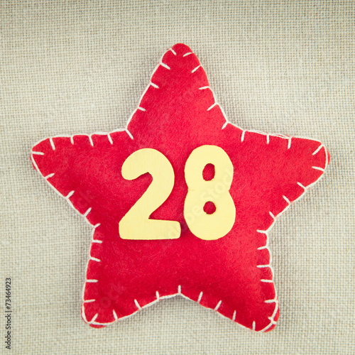 Fotografia  Red star with wooden number 28 on vintage fabric background