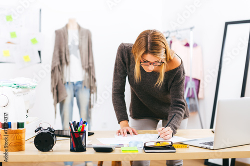 Plakat  designer working with a laptop at home