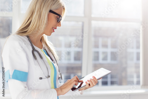 Photo  Female doctor looking at medical records on tablet computer