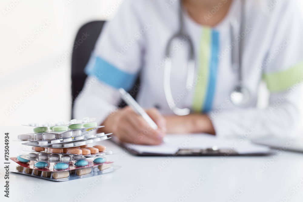Fotografering  Doctor writing many medicine prescriptions