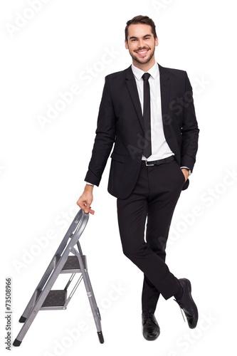 Fotografía  Smiling businessman leaning on stepladder