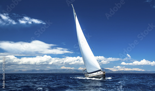Photo Sailing ship yachts with white sails in the open sea.
