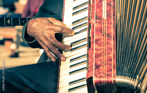 Photo African musician hand playing fisarmonica - Street artist