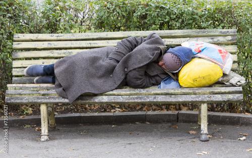 Fototapeta Homeless man sleeping on a bench