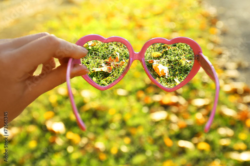 Tuinposter Zwavel geel Vision concept. Glasses in hand on green grass background