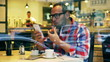 Man eating sandwich and texting on smartphone, steadycam shot
