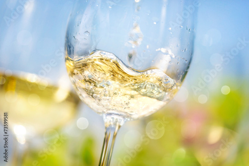 Pouring white wine in a glass Poster