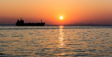 Silhouette Of The Cargo Ship Over The Sunset