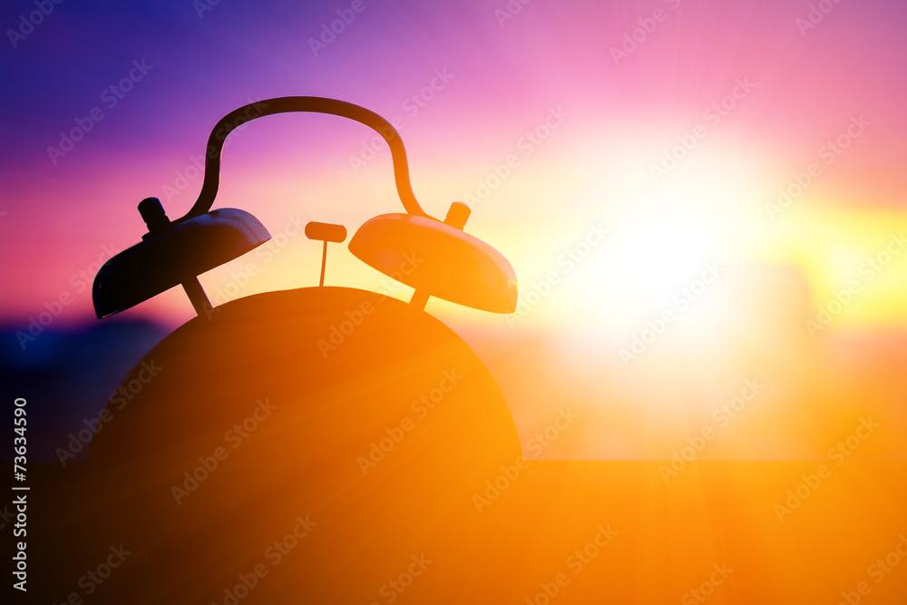 Fototapeta alarmclock silhouette at sunrise cityscape