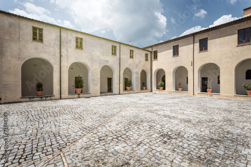 Fotografie, Obraz  Empty cobblestone court surrounded by arcades