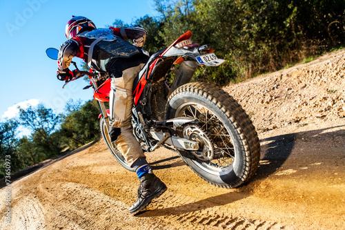 Photo  Motocross bike taking off on dirt road.