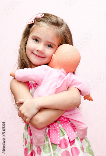 Fotografie, Obraz  Cute little girl holding and embracing her doll