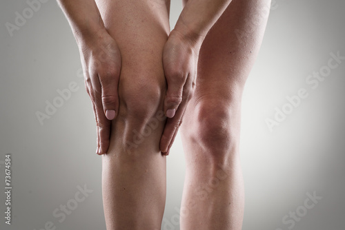 Woman touching her injured knee. Rheumatism or arthrosis. Wallpaper Mural