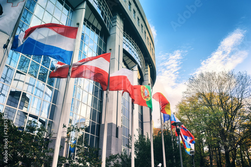 Waiving flags in front of European Parliament building. Brussels Wallpaper Mural