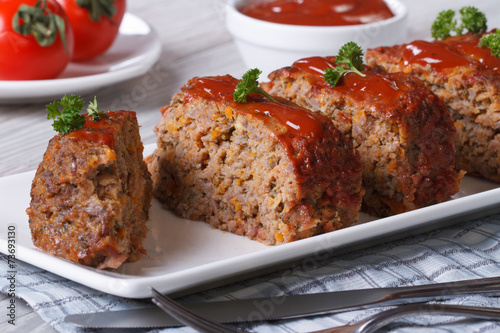 Photo  Sliced meat loaf with ketchup and parsley close-up