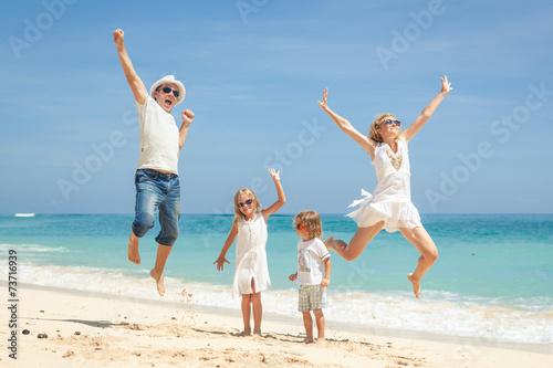 Plakat Szczęśliwy rodzinny doskakiwanie na plaży w dnia czasie