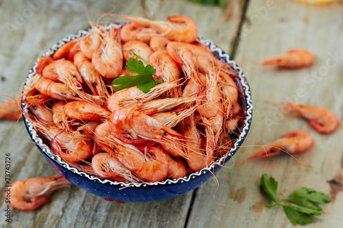 Papiers peints Coquillage Prepared shrimp on blue plate on wooden background