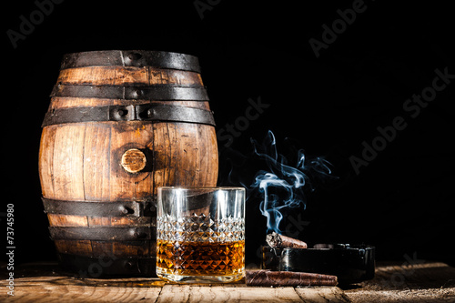Carta da parati Glass of alcohol and smoking noble cigar on a black background