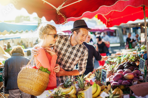 Poster Cuisine a young couple buying fruits and vegetables at a market