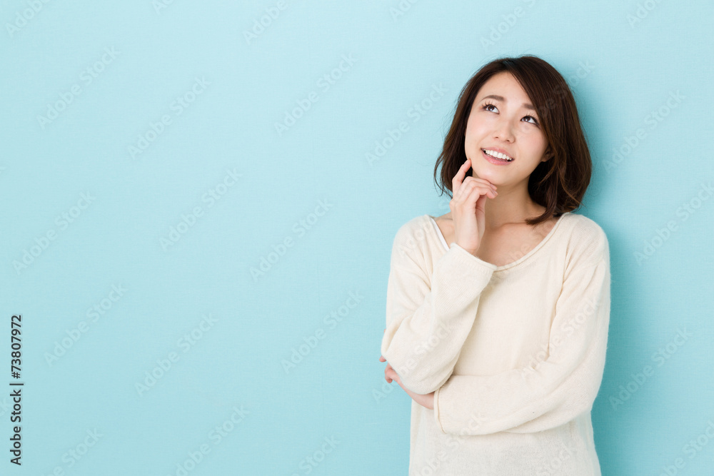 Fototapeta attractive asian woman thinking on blue background