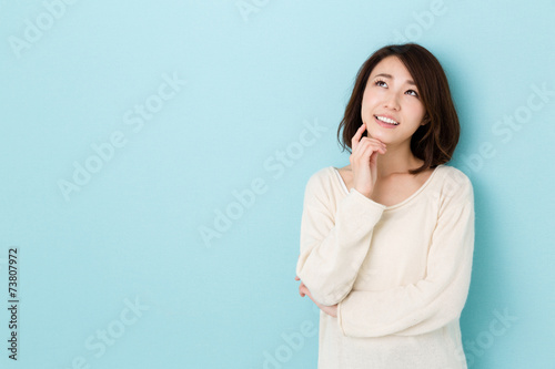 attractive asian woman thinking on blue background Poster