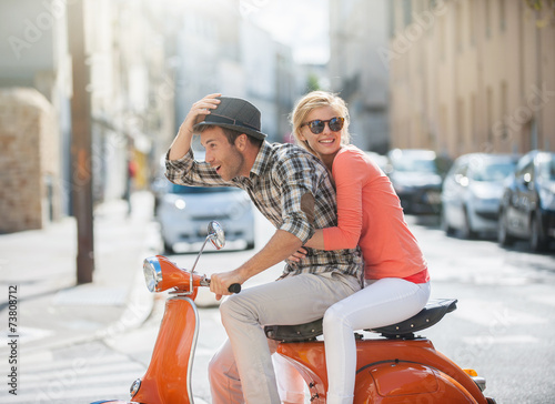 Photo  glamorous couple on a scooter in the street