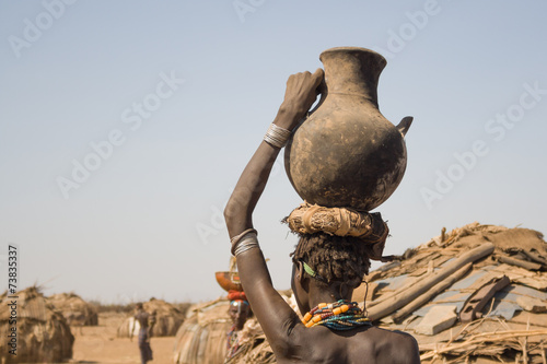 Woman carries on her head a container with water, Ethiopia