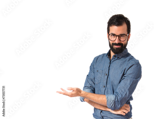 Fotografía  Young hipster man presenting something over white background