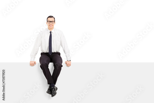Young businessman sitting on a blank billboard