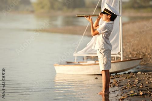 Fényképezés  Boy captain looking through a telescope at the lake