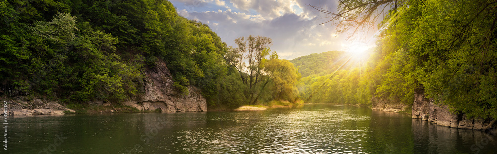 forest river with stones on shores at sunset