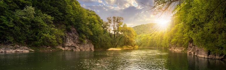 rzeka las z kamieniami na brzegach o zachodzie słońca