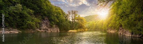 Montage in der Fensternische Fluss forest river with stones on shores at sunset