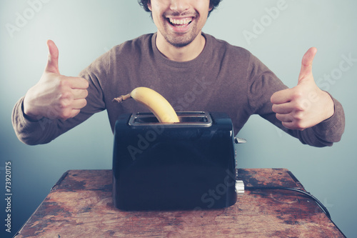 Valokuva  Young man toasting banana giving thumbs up