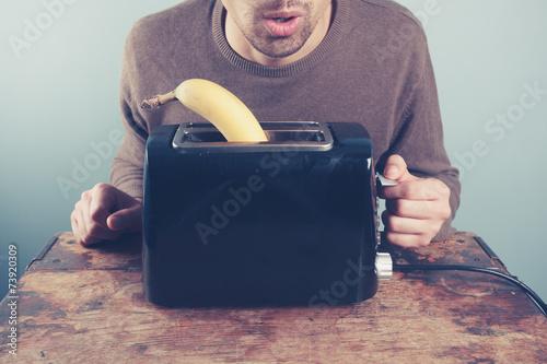 Valokuvatapetti Young man trying to toast a banana