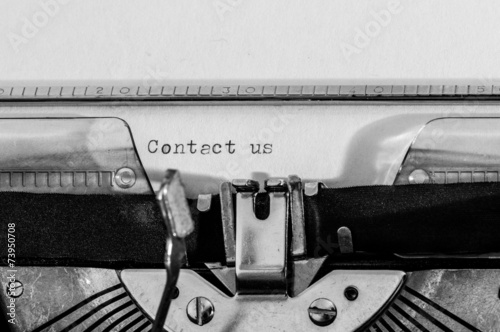 """Photo  Old typewriter with the """"Contact us"""" text typed on a white paper"""