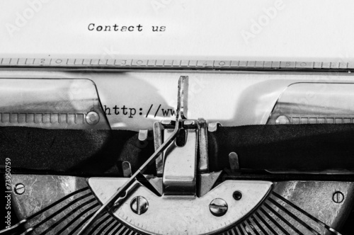 """Photo  Typewriter with the """"Contact us"""" text typed on a white paper."""