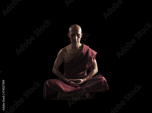 buddhist monk in meditation pose over black background Canvas