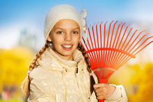 Close Up View Of Smiling Girl With Red Rake