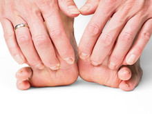 Hands Pulling Toes On Barefoot Feet With Shadow Effect