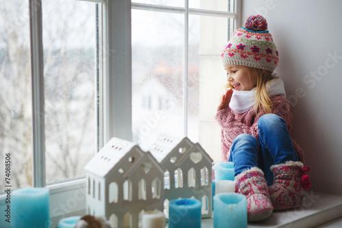 usmiechajaca-sie-dziewczynka-w-zimowym-ubraniu-na-parapecie