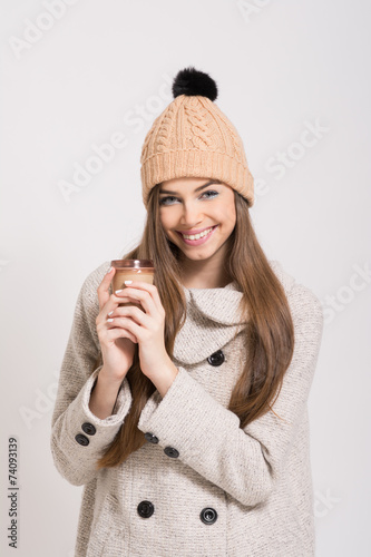 Valokuva  Teenage girl with beanie hat and takeaway coffee. No retouch.
