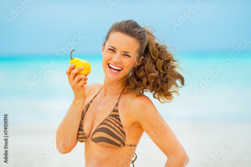 Poster Lieu connus d Asie Portrait of smiling young woman with pear on beach