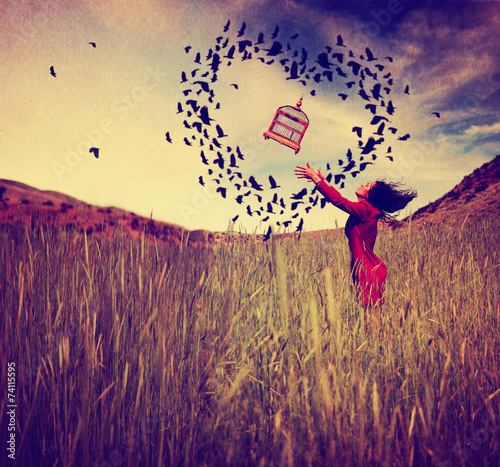 Fotografia  a girl in a field tossing a birdcage in the air with birds