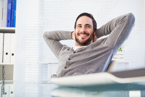 Fotografía  Relaxed casual businessman leaning back at his desk