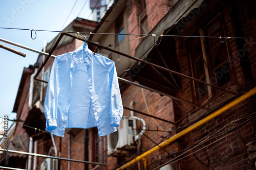 Blue shirt hanging on a washing line in the old town of Shanghai Poster
