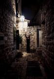 Fototapeta Uliczki - woman walking on narrow street lit by gas lantern