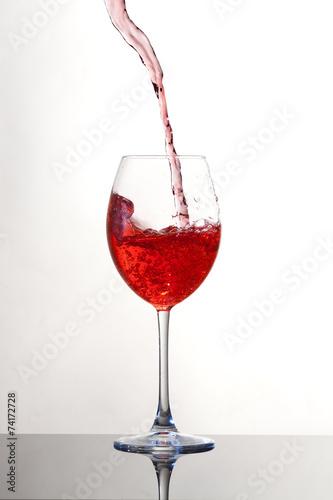 Fotografie, Obraz  Vino che viene versato in un calice, sfondo bianco