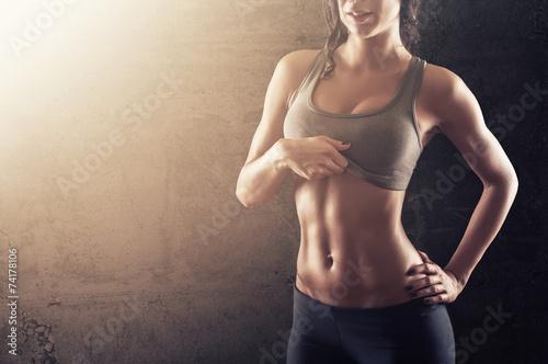 Fotografie, Obraz  Přizpůsobit mladá žena ukazuje její abs