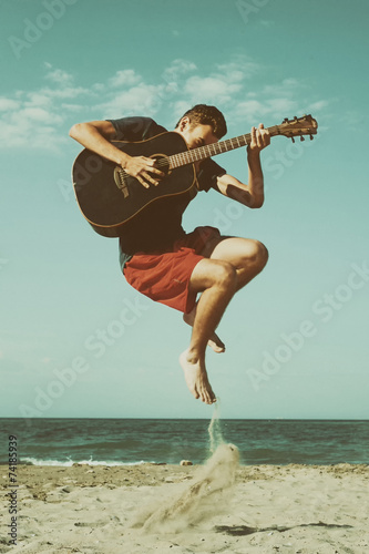 Boy playing guitar on the beach Tablou Canvas